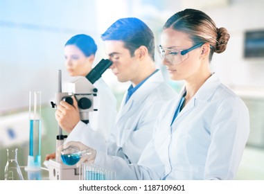 Female and male scientists in glasses working