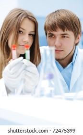 A female and male scientists working in a Lab with a test tubes