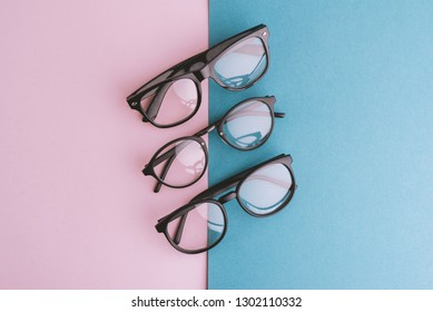 Female, Male set of eyeglasses on pink blue background. Flat lay, top view.