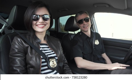 Female and male smiling police officers with badges sitting in car