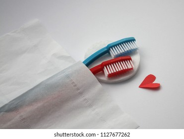 Female and male toothbrushes hugging in bed, visual metaphore of love.
