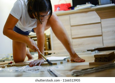 Female in male work concept. Handyman woman. The woman in the living room makes a working one for the beginning of the school year with a hammer and a screwdriver.