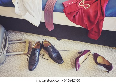 Female and man footwear and clothing in a hotel room, vintage toned conceptual picture.