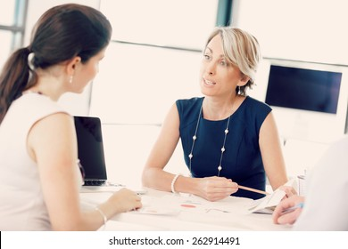 Female manager assessing work of her employees