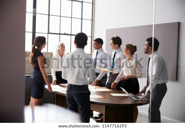 Female manager and business team standing in a  meeting room
