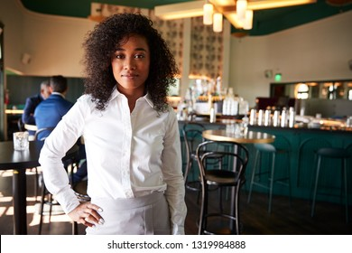 Female Manager Of Busy Cocktail Bar In Restaurant With Customers At Camera