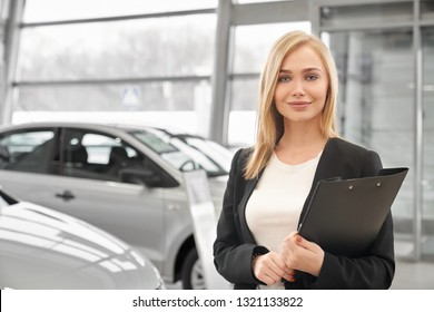 Female manager of car dealership standing in showroom and posing. Pretty woman with blonde hair smiling, looking at camera. Car dealer holding black folder in hands.