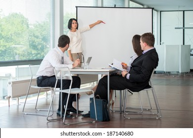 Female manager delivering presentation to a team of coworkers