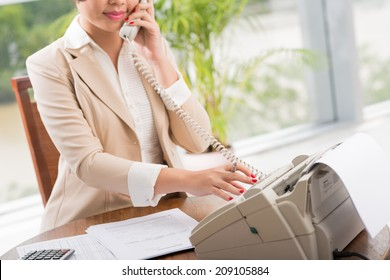 Female manager dialing number on the fax machine