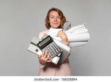 Female manager with different office stuff on grey background