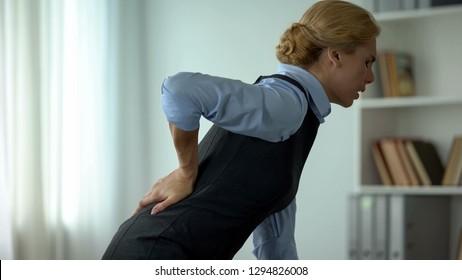 Female manager feeling sharp pain in loins, sedentary life on work result