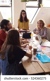 Female Manager Leads Meeting Around Table In Design Office