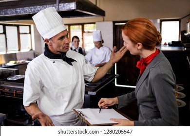 Female manager and male chef interacting with each other in kitchen at hotel