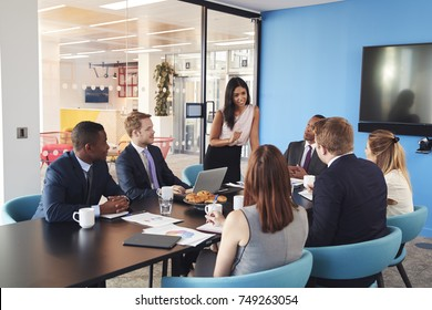 Female manager stands addressing colleagues in meeting room