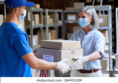 Female manager supervisor wearing face mask preparing fast drop shipping safe delivery giving parcels packages boxes to male courier taking ecommerce orders to deliver standing in warehouse storage.