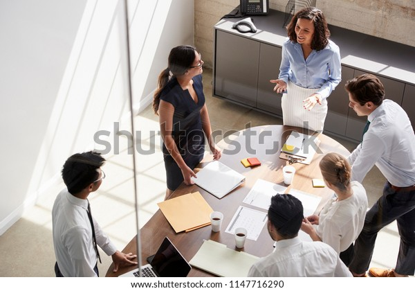 Female manager in team meeting, elevated view through window