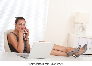 Female manager working with legs on table at the office