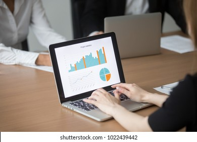 Female manager working on laptop at team meeting analyzing marketing result financial statistics report on screen, business software for project management data analysis, close up over shoulder view
