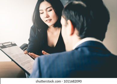 Female mananger is offering a new employee to sign work contract