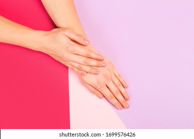 female  manicure. Beautiful young woman's hands on color pink  background