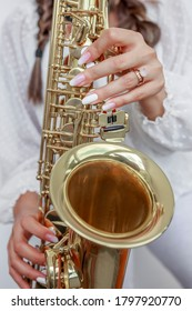 Female with manicure playing saxophone