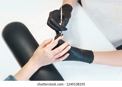 Female manicurist cleaning cuticle with professional manicure pusher tool. Nail care. Closeup of beautiful woman hands getting manicure in spa salon.
