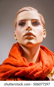 Female mannequin in display window wearing a red scarf.