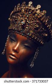 Female Mannequin in golden crown with beads on dark background