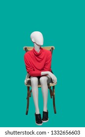 Female mannequin sitting on bentwood chair, isolated on green background. No brand names or copyright objects.
