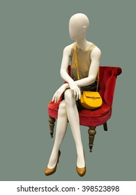 Female mannequin sitting on red armchair, against green background. No brand names or copyright objects.
