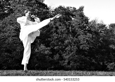Female martial artist practicing Taekwondo outdoors