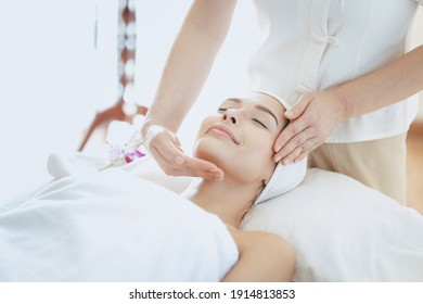 Female massage therapist giving a massage at a spa. Young woman receiving head and facial massage in spa salon.