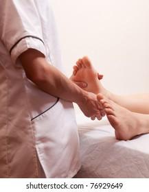 A female masseur giving a foot massage in a dayspa