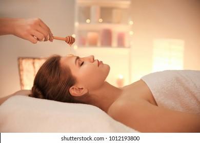 Female masseur using honey for spa procedure in salon