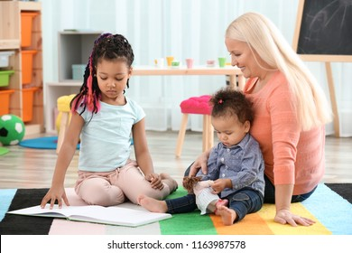 Female mature nanny with little African-American sisters in room