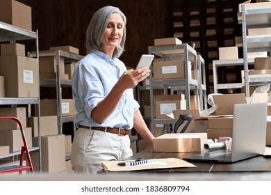 Female mature senior small business owner using mobile app checking parcel box. Older entrepreneur seller holding cell phone tech device preparing retail package postal shipping order in warehouse.