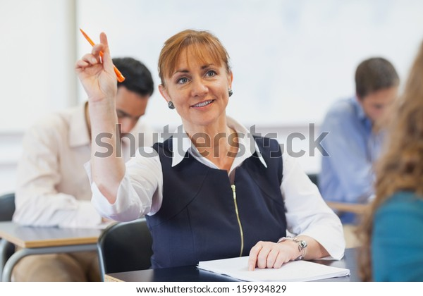 Female mature student raising her hand while sitting in classroom