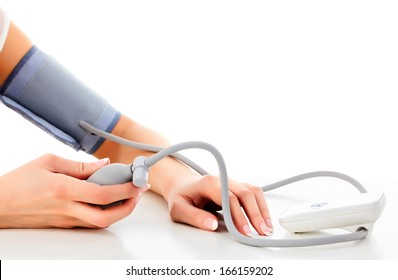 Female measures her blood pressure, white background, copyspace