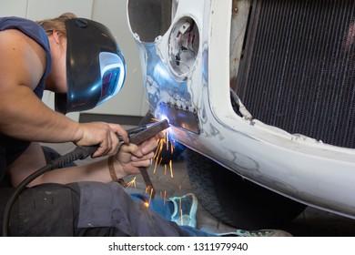 Female mecanic welding classic car
