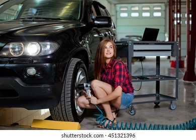 Female mechanic changing tire with air impact wrench