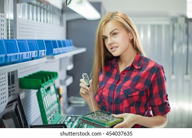 Female mechanic in checked shirt. Auto service station. Young sexy brunette woman working with electronic plate