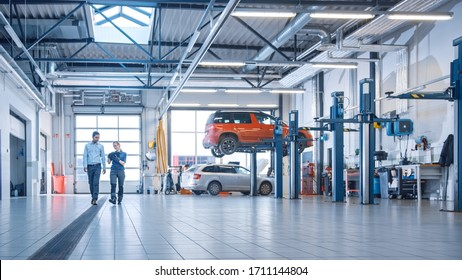 Female Mechanic Checks Diagnostics Results on a Tablet Computer and Explains a Vehicle Breakdown to a Manager. Car Service Employees Talk while Walking in a Garage. Modern Clean Workshop.