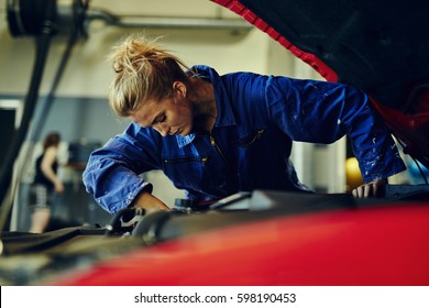 Female mechanic fixing a red sports car
