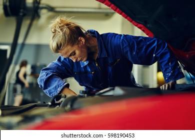 Female mechanic fixing a red sports car
