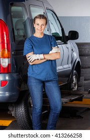 Female Mechanic Standing Arms Crossed By Car