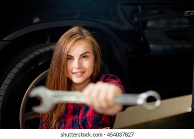 Female mechanic at work. auto service station. Young woman working in the garage.