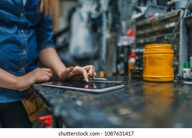 Female mechanic at work. Using a tablet while fixing a bicycle. Female bicycle repair technician using digital tablet in bicycle shop. Mechanic woman checking something on a tablet-pc and checklist.