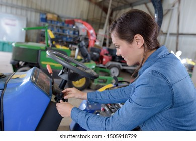 female mechanic working on lawnmower in workshop