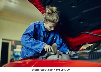 Female mechanic working on red sports car