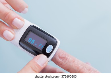 Female medic and old woman patient using medical device called finger pulse oximeter. From below, close-up. Unrecognizable